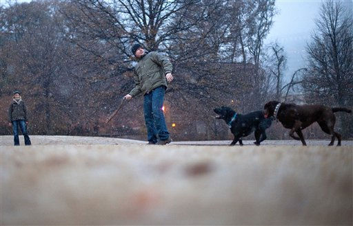 Aaron Curtis, of Atlanta, throws a stick for his dogs, Boone, left, and Einstein, as Jennifer Glavis, left, looks on, as they play in the snow in Atlanta&#39;s Piedmont Park Saturday, Dec. 25, 2010. &#40;AP Photo&#47;David Goldman&#41; <span class=meta>(AP Photo&#47; David Goldman)</span>