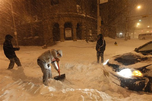 Jose Carlos Xochitiltecatl, center, shovels snow to make way for Khaaliq Spann&#39;s vehicle which was stuck in high snow in Downtown Newark, Monday, Dec. 27, 2010, in Newark, N.J. &#40;AP Photo&#47;Julio Cortez&#41; <span class=meta>(AP Photo&#47; Julio Cortez)</span>