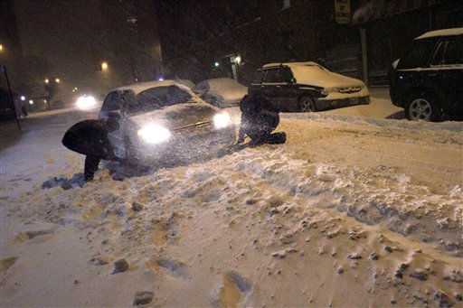 Men dig a car stuck in the snow in the East Village neighborhood of Manhattan, Sunday, Dec. 26, 2010 in New York. &#40;AP Photo&#47;Mary Altaffer&#41; <span class=meta>(AP Photo&#47; Mary Altaffer)</span>