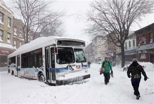 People pass a city bus stuck in the snow, Monday, Dec. 27, 2010 in the Brooklyn borough of New York. A powerful East Coast blizzard menaced would be travelers Monday. Two buses and two sanitation trucks were stuck on the same block in the Park Slope neighborhood of Brooklyn. &#40;AP Photo&#47;Mark Lennihan&#41; <span class=meta>(AP Photo&#47; Mark Lennihan)</span>