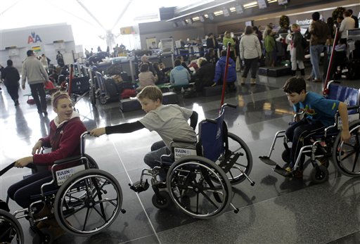 After their flight to Finland was canceled, players from the Skaneateles Bantam Finland hockey team pass the time by trying out the wheelchairs at John F. Kennedy International Airport in New York, Monday, Dec. 27, 2010.  &#40;AP Photo&#47;Seth Wenig&#41; <span class=meta>(AP Photo&#47; Seth Wenig)</span>