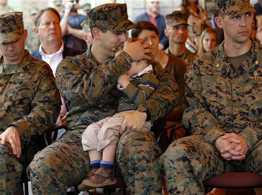 U.S. Navy Petty Officer 2nd Class Patrick Quill, center, kisses his 2-year-old son, Zack, while waiting to receive the Silver Star medal with two other recipients, U.S. Marine Sgt. Frankie Shinost, left, and U.S. Marine Maj. James Rose, right, during a ceremony held at Camp Pendleton, Calif., Monday, Dec. 3, 2012. The three received the medals for their heroism while serving in Afghanistan. &#40;AP Photo&#47;Jae C. Hong&#41; <span class=meta>(AP Photo&#47; Jae C. Hong)</span>