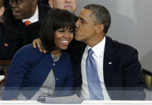 President Barack Obama kisses first lady Michelle Obama in the presidential box near the White House as bands march past the presidential box, Monday, Jan. 21, 2013, in Washington. Thousands  marched during the 57th Presidential Inauguration parade after the ceremonial swearing-in of President Barack Obama. &#40;AP Photo&#47;Gerald Herbert&#41; <span class=meta>(AP Photo&#47; Gerald Herbert)</span>