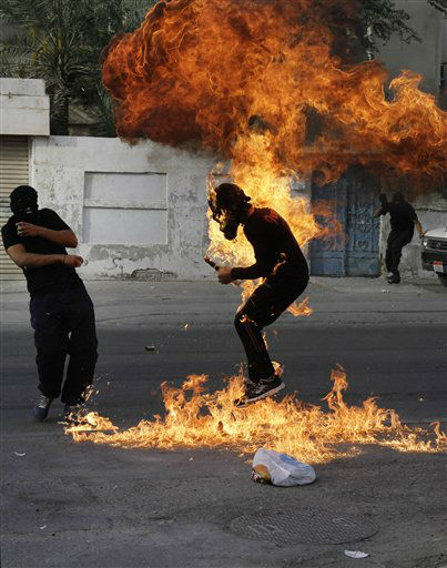 "<div class=""meta ""><span class=""caption-text "">A Bahraini anti-government protester is engulfed in flames when a shot fired by riot police hit the petrol bomb in his hand that he was preparing to throw during clashes in Sanabis, Bahrain, Thursday, March 14, 2013. Protests and clashes erupted in opposition areas nationwide Thursday with government opponents observing a ""Dignity Strike"" _ blocking roads, closing shops, protesting and staying home from work and school _ called by the more radical February 14 youth group. (AP Photo/Hasan Jamali) (AP Photo/ Hasan Jamali)</span></div>"