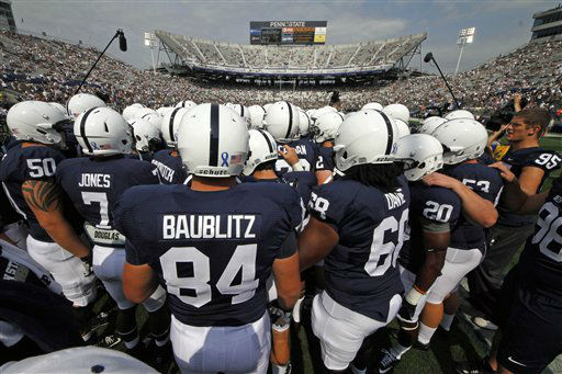 The Penn State football team gathers  during warmups before their season opening NCAA college football game against Ohio at Beaver Stadium in State College, Pa., Saturday, Sept. 1, 2012. The blue ribbon on the back of helmets is to show support for child abuse victims. &#40;AP Photo&#47;Gene J. Puskar&#41; <span class=meta>(AP Photo&#47; Gene J. Puskar)</span>