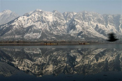 Kashmiris row their traditional boats with a backdrop of snow-covered mountains on the Dal Lake in Srinagar, India, Sunday, Jan. 2, 2011. &#40;AP Photo&#47;Mukhtar Khan&#41; <span class=meta>(AP Photo&#47; Mukhtar Khan)</span>