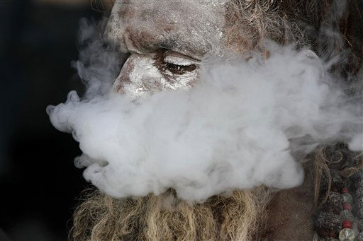 A sadhu, or Hindu holy man, smokes marijuana at a transit camp in Calcutta, India, Thursday, Jan. 6, 2011. Pilgrims are arriving in the city before proceeding onward for an annual holy dip at Gangasagar, the confluence of Ganges River and Bay of Bengal, some 140 kilometer &#40;87 miles&#41; south of Calcutta, on the occasion of Makar Sankranti that falls on Jan. 14. &#40;AP Photo&#47;Bikas Das&#41; <span class=meta>(AP Photo&#47; Bikas Das)</span>