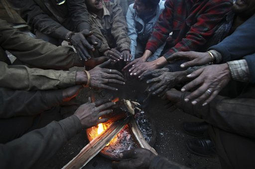 Indian workers warm their hands around a fire in Jammu, India, Monday, Jan. 10, 2011. Near-freezing temperatures and icy Himalayan winds killed 13 people overnight in northern India, bringing the death toll to nearly 100 from a cold snap that began three weeks ago, police said Monday. &#40;AP Photo&#47;Channi Anand&#41; <span class=meta>(AP Photo&#47; Channi Anand)</span>
