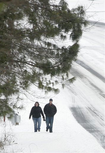 Lee Chirisman, left, and Anthony Burt take advantage of the lack of traffic and walk along the side of normally busy Pleasant Hill Road after an overnight winter storm blanketed the area with snow Monday, Jan. 10, 2011, in Duluth, Ga. &#40;AP Photo&#47;John Amis&#41; <span class=meta>(AP Photo&#47; John Amis)</span>