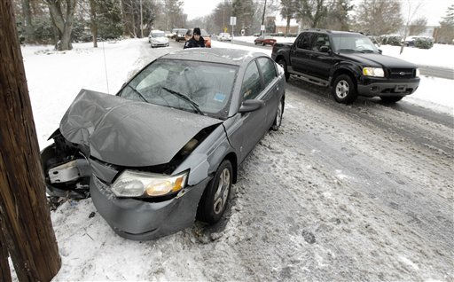 A police officer examines the wreckage of a car after it slid into a power pole during a snowstorm in Charlotte, N.C., Monday, Jan. 10, 2011. Sleet, ice and several inches of snow _ as much as 9 inches in some places _ blanketed states from Louisiana to the Carolinas mostly unaccustomed to arctic weather and caused at least three deaths and left thousands without power. &#40;AP Photo&#47;Chuck Burton&#41; <span class=meta>(AP Photo&#47; Chuck Burton)</span>