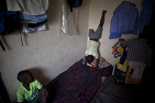 "<div class=""meta ""><span class=""caption-text "">Sebastian Lamoth, 8, right, scales a wall at his home as he plays with his cousin, Cassius Bill Herold, in Port-au-Prince, Haiti, Monday Jan. 10, 2011. Lamoth's leg was amputated due to an injury suffered in the Jan. 12, 2010 earthquake. Almost one year has passed since the magnitude-7.0 quake that killed more than 220,000 people and left millions homeless. (AP Photo/Ramon Espinosa) (AP Photo/ Ramon Espinosa)</span></div>"