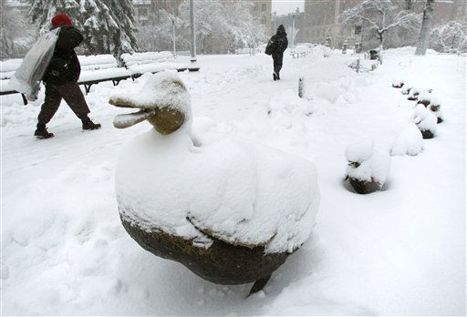 "<div class=""meta image-caption""><div class=""origin-logo origin-image ""><span></span></div><span class=""caption-text"">Pedestrians walk past the snow covered ""Make Way for Ducklings"" statues at the Public Garden in Boston, Wednesday, Jan. 12, 2011. The Boston area is expected to receive well over a foot of snow during a day long winter storm.(AP Photo/Charles Krupa) (AP Photo/ Charles Krupa)</span></div>"