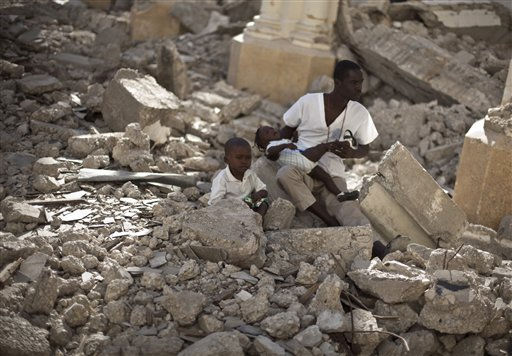 "<div class=""meta image-caption""><div class=""origin-logo origin-image ""><span></span></div><span class=""caption-text"">A man with two children sits in the rubble of the earthquake damaged Cathedral during a mass in Port-au-Prince, Haiti, Wednesday Jan. 12, 2011.  Wednesday marks the one year anniversary since Haiti's magnitude-7.0 earthquake that devastated the capital and is estimated to have killed more than 230,000 people and left millions homeless.  (AP Photo/Ramon Espinosa) (AP Photo/ Ramon Espinosa)</span></div>"