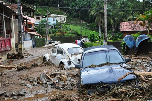 Cars sit in debris in a flooded street in Teresopolis, Rio de Janeiro state, Brazil, Wednesday Jan. 12, 2011. Torrential summer rains tore through Rio de Janeiro state's mountains, killing at least 140 people in 24 hours, Brazilian officials said Wednesday. (AP Photo/Roberto Ferreira, Agencia O Dia)   --------------------------------------------------------------------------------