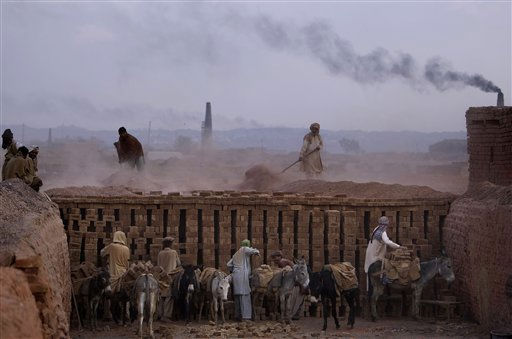 Pakistani men work in a brick factory on the outskirts of Islamabad, Pakistan, Thursday, Jan. 13, 2011. (AP Photo/Muhammed Muheisen)