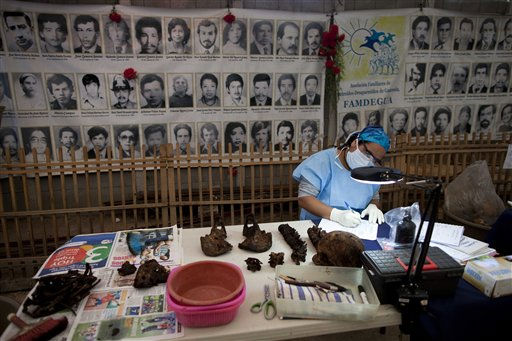 Forensic anthropologist Alma Vasquez analyzes exhumed bones removed from a mass grave in one of Guatemala City's largest cemeteries, La Verbena, Thursday Jan. 13, 2011. A group of forensic anthropologists expect to create a database that will eventually help match genetic samples of relatives of the more than 40,000 persons disappeared during the civil war. (AP Photo/Rodrigo Abd)