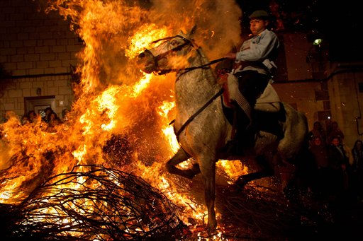 A man rides a horse through a bonfire in San Bartolome de Pinares, Spain, on Sunday, Jan. 16, 2011, during a traditional festival in honor of Saint Anthony, the patron saint of animals.&#40;AP Photo&#47;Arturo Rodriguez&#41; <span class=meta>(AP Photo&#47; Arturo Rodriguez)</span>