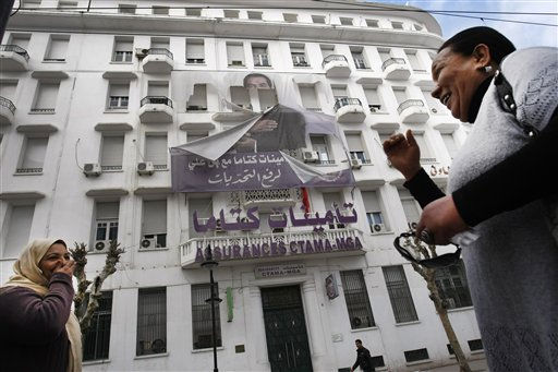 "<div class=""meta ""><span class=""caption-text "">Women smile as they walk past to torn photo of former Tunisian President Zine El Abidine Ben Ali in the center of Tunis, Sunday, Jan. 16. 2011. Tunisia sped toward a new future after its iron-fisted leader fled, with an interim president sworn in and ordering the country's first multiparty government to be formed. (AP Photo/Christophe Ena) (AP Photo/ Christophe Ena)</span></div>"