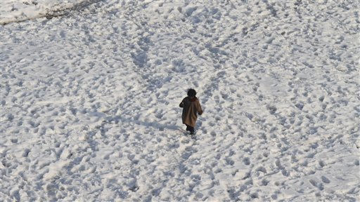 A Kashmiri girl walks on a snow covered field in Srinagar, India, Sunday, Jan. 16, 2011. Police say near-freezing temperatures and Himalayan winds killed at least 13 homeless people in northern India, raising the death toll from a severe cold spell to 129. &#40;AP Photo&#47;Mukhtar Khan&#41; <span class=meta>(AP Photo&#47; Mukhtar Khan)</span>