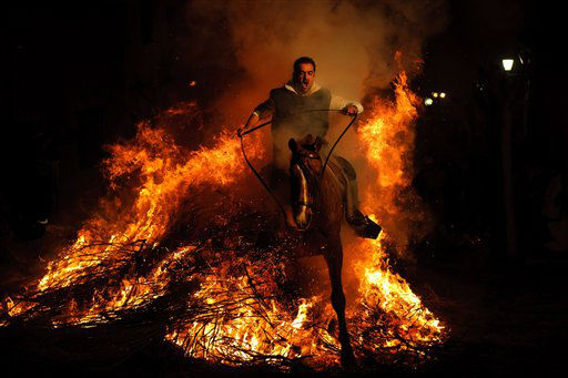 A man rides a horse through a bonfire in San Bartolome de Pinares, Spain, Monday, Jan. 16, 2012, in honor of Saint Anthony, the patron saint of animals. On the eve of Saint Anthony&#39;s Day, hundreds ride their horses trough the narrow cobblestone streets of the small village of San Bartolome during the &#34;Luminarias,&#34; a tradition that dates back 500 years and is meant to purify the animals with the smoke of the bonfires and protect them for the year to come. &#40;AP Photo&#47;Daniel Ochoa de Olza&#41; <span class=meta>(AP Photo&#47; Daniel Ochoa de Olza)</span>