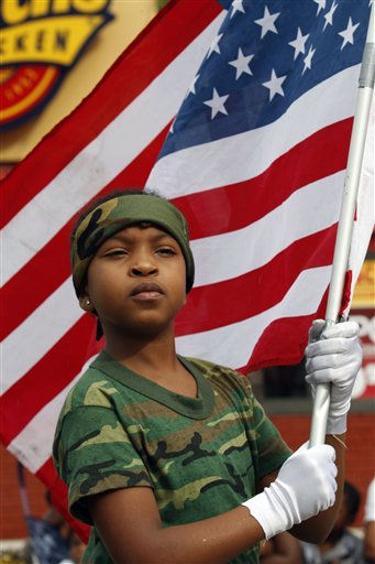 Jahnae Everett, 10, carries the American flag as she and a group of &#34;Major Pain&#39;s Kids,&#34; a program for at-risk youth, prepare to march in a parade honoring the Rev. Martin Luther King Jr., Monday, Jan. 17, 2011 in the Liberty City neighborhood of Miami. &#40;AP Photo&#47;Wilfredo Lee&#41; <span class=meta>(AP Photo&#47; Wilfredo Lee)</span>