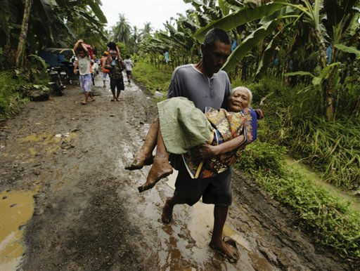 "<div class=""meta image-caption""><div class=""origin-logo origin-image ""><span></span></div><span class=""caption-text"">Rescuers and volunteers help an elderly woman to an evacuation center following flooding caused by the continued rains brought about by the cold front in the central and southeatern parts of the country, at Sta. Cruz township, Davao del Sur province in southern Philippines, Tuesday Jan. 18, 2011. A flash flood Monday night swept at least 100 houses in four villages of this town, killing three persons bringing to 56 the number of people killed following weeks of heavy rains and subsequent floodings in several provinces in central and southern Philippines. (AP Photo/Froilan Gallardo) (AP Photo/ Froilan Gallardo)</span></div>"