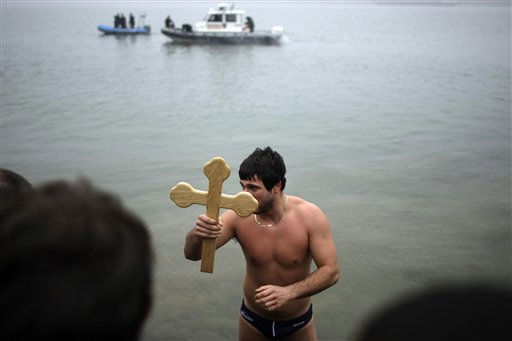 Nikola Kovacevic, 21, center, lifts up a wooden cross as he reaches the shoreline, after being the first to reach the cross and retrieving it from the river Danube,  in Belgrade, Serbia, Wednesday, Jan. 19, 2011.  The retrieval of the cross which is cast into the water,  is an annual event that marks the Orthodox Epiphany commemorating Christ&#39;s baptism. &#40;AP Photo&#47;Marko Drobnjakovic&#41; <span class=meta>(AP Photo&#47; Marko Drobnjakovic)</span>
