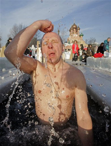 A Russian crosses himself as he emerges from an ice hole made in the shape of a cross in a traditional Epiphany celebration in Moscow, Wednesday, Jan. 19, 2011. Thousands of Russian Orthodox Church followers plunged into icy rivers and ponds across the country to mark the  Epiphany, cleansing themselves with water deemed holy for the day. Water that is blessed by a cleric on Epiphany is considered holy and pure until next year&#39;s celebration, and is believed to have special powers of protection and healing. The Russian Orthodox Church follows the old Julian calendar, according to which Epiphany falls on Jan. 19.  Moscow temperatures on Wednesday morning dropped to -13 C &#40; 9 F&#41;. &#40;AP Photo&#47; Alexander Zemlianichenko Jr&#41; <span class=meta>(AP Photo&#47; Alexander Zemlianichenko Jr)</span>