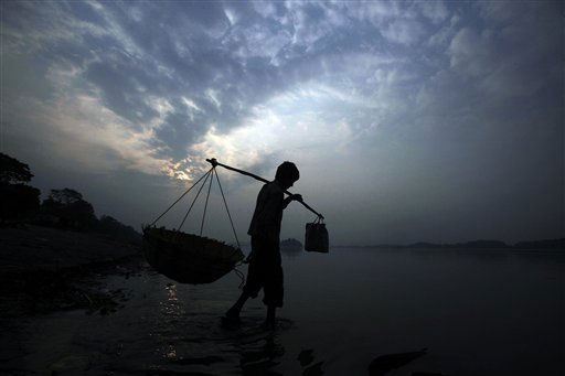 A vegetable seller walks in the Brahmaputra River in Gauhati, India, Sunday, Jan. 23, 2011. &#40;AP Photo&#47;Anupam Nath&#41; <span class=meta>(AP Photo&#47; Anupam Nath)</span>