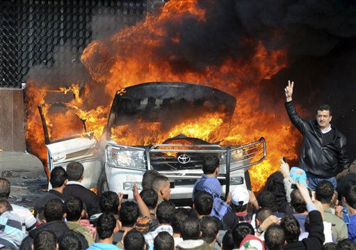 Angry protesters burn a van belonging to Al-Jazeera in the northern port city of Tripoli, Lebanon, Tuesday, Jan. 25, 2011. Thousands of Sunnis waved flags, burned tires and torched a van belonging to Al-Jazeera on Tuesday during a &#34;day of rage&#34; to protest gains by the Shiite militant group Hezbollah, which now has enough support in parliament to control Lebanon&#39;s next government. &#40;AP Photo&#41; <span class=meta>(AP Photo&#47; STR)</span>