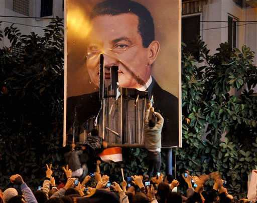 Demonstrators deface a poster of  Egyptian President Hosni Mubarak in Alexandria Egypt, Tuesday Jan. 25, 2011. Thousands of protesters  marched in  Alexandria Tuesday  in what was dubbed a &#34;Day of Rage&#34; against Mubarak and lack of political freedoms under his rule. &#40;AP Photo&#41; <span class=meta>(AP Photo&#47; Anonymous)</span>