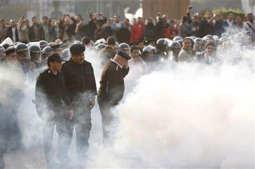 Police are engulfed by their own tear gas at a demonstration in Cairo, Egypt Tuesday, Jan. 25, 2011. Thousands of anti-government protesters, some hurling rocks and climbing atop an armored police truck, clashed with riot police Tuesday in the center of Cairo in a Tunisia-inspired demonstration to demand the end of Hosni Mubarak&#39;s nearly 30 years in power. &#40;AP Photo&#47;Nasser Nasser&#41; <span class=meta>(AP Photo&#47; Nasser Nasser)</span>