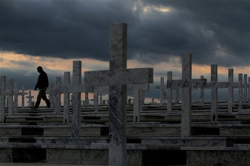 A worker walks by newly-dug graves that will receive the recently identified remains of Greek Cypriots who had been listed as missing since the 1974 Turkish invasion of Cyprus, at Tymvos Makedonitissas military cemetery in the island&#39;s divided capital Nicosia, on Wednesday, Jan. 26, 2011.  The U.N. chief Ban Ki-moon emerged from a meeting Wednesday between Greek Cypriot President Dimitris Christofias and Turkish Cypriot leader Dervis Eroglu, expressing optimism over reunification talks that could determine the outcome of Turkey&#39;s troubled bid to join the European Union. Cyprus was split into a Turkish Cypriot north and a Greek Cypriot south in 1974.&#40;AP Photo&#47;Petros Karadjias&#41; <span class=meta>(AP Photo&#47; Petros Karadjias)</span>