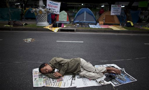"<div class=""meta ""><span class=""caption-text "">A supporter of the People's Alliance for Democracy, also known as the Yellow Shirts, sleeps on the street near Government House in Bangkok, Thailand, Thursday Jan. 27, 2011. The protesters have camped out again near Government House demanding among others that a pact with Cambodia on settling border disputes be revoked.  Prime Minister Abhisit Vejjajiva has rejected the demands. Thailand has seen a number of prolonged and often violent street protest since 2006. (AP Photo/David Longstreath) (AP Photo/ David Longstreath)</span></div>"