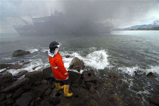 "<div class=""meta ""><span class=""caption-text "">A firefighter looks at thick smoke billow from a ferry that caught fire off Java island, in Serang, Banten province, Indonesia, Friday, Jan. 28, 2011. The crowded ferry caught fire early Friday sending panicked passengers jumping into the sea, officials said. (AP Photo) (AP Photo/ Anonymous)</span></div>"