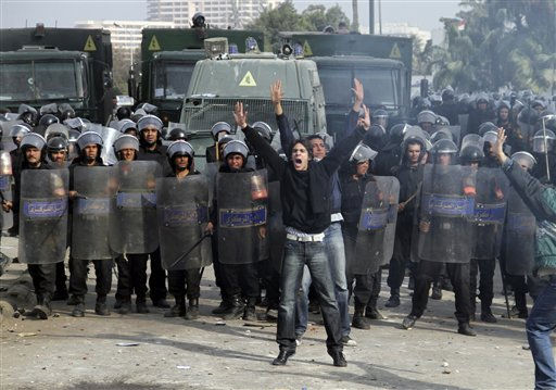 A Egyptian protesters shout in front of anti-riot policemen who block a bridge in Cairo, Egypt, Friday, Jan. 28, 2011. The Egyptian capital Cairo was the scene of violent chaos Friday, when tens of thousands of anti-government protesters stoned and confronted police, who fired back with rubber bullets, tear gas and water cannons. It was a major escalation in what was already the biggest challenge to authoritarian President Hosni Mubarak&#39;s 30 year-rule. &#40;AP Photo&#47;Ahmed Ali&#41; <span class=meta>(AP Photo&#47; Ahmed Ali)</span>