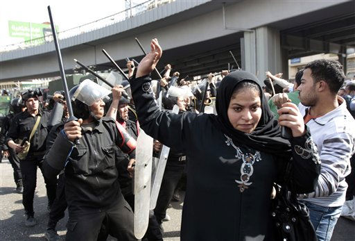 An Egyptian woman flees as Egyptian anti-riot policemen clash with protesters in Cairo, Egypt, Friday, Jan. 28, 2011. The Egyptian capital Cairo was the scene of violent chaos Friday, when tens of thousands of anti-government protesters stoned and confronted police, who fired back with rubber bullets, tear gas and water cannons.  &#40;AP Photo&#47; Lefteris Pitarakis&#41; <span class=meta>(AP Photo&#47; Lefteris Pitarakis)</span>