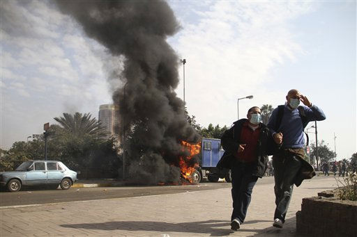 "<div class=""meta image-caption""><div class=""origin-logo origin-image ""><span></span></div><span class=""caption-text"">Egyptian protesters flee past a burning vehicle in Cairo, Egypt, Friday, Jan. 28, 2011. The Egyptian capital Cairo was the scene of violent chaos Friday, when tens of thousands of anti-government protesters stoned and confronted police, who fired back with rubber bullets, tear gas and water cannons. It was a major escalation in what was already the biggest challenge to authoritarian President Hosni Mubarak's 30 year-rule. (AP Photo/Ahmed Ali) (AP Photo/ Ahmed Ali)</span></div>"