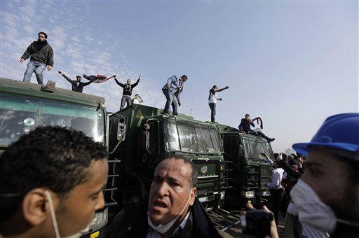 Egyptian anti-government activists are seen atop police trucks during clashes with police in Cairo, Egypt, Friday, Jan. 28, 2011. Tens of thousands of anti-government protesters poured into the streets of Egypt Friday, stoning and confronting police who fired back with rubber bullets and tear gas in the most violent and chaotic scenes yet in the challenge to President Hosni Mubarak&#39;s 30-year rule. &#40;AP Photo&#47;Ben Curtis&#41; <span class=meta>(AP Photo&#47; Ben Curtis)</span>