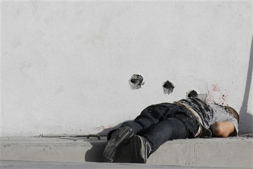 A man&#39;s body lies on the sidewalk by a wall pierced with bullet holes and splattered with blood in the municipality of Santa Catarina on the outskirts of Monterrey, Mexico, Tuesday Feb. 1, 2011. Three people were shot to death in the area.  &#40;AP Photo&#47;Carlos Jasso&#41; <span class=meta>(AP Photo&#47; Carlos Jasso)</span>