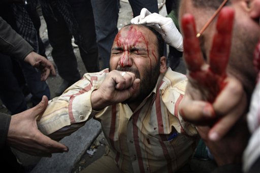 "<div class=""meta ""><span class=""caption-text "">A wounded anti-government protestor is tended during clashes in Cairo, Egypt, Thursday, Feb. 3, 2011. Another bout of heavy gunfire and clashes erupted Thursday around dusk in the Cairo square at the center of Egypt's anti-government chaos, while new looting and arson spread around the capital. Gangs of thugs supporting President Hosni Mubarak attacked reporters, foreigners, and human rights workers and the army rounded up foreign journalists. (AP Photo/Sebastian Scheiner) (AP Photo/ Sebastian Scheiner)</span></div>"