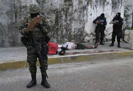 Mexican navy and federal police personnel take notes at the scene where the bodies of two men were dumped in the Pacific coast resort city of Acapulco, Mexico, Saturday Feb. 5, 2011. The two bodies had their heads bound in plastic tape and their hands and feet bound with gaffer tape. They had been shot in the head and neck and a warning message to a rival drug gang was left behind. &#40;AP Photo&#47;Bernandino Hernandez&#41; <span class=meta>(AP Photo&#47; Bernandino Hernandez)</span>