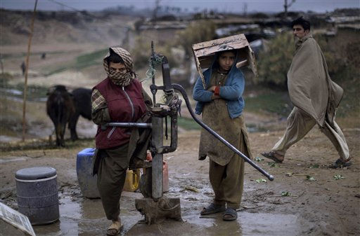 Pakistani boys stand by a hand pump as they wait for other boys to fetch water on a rainy day in a poor neighborhood on the outskirts of Islamabad, Pakistan, Sunday, Feb. 6, 2011. &#40;AP Photo&#47;Muhammed Muheisen&#41; <span class=meta>(AP Photo&#47; Muhammed Muheisen)</span>