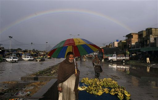 A full rainbow appears in the sky, as Pakistani banana vendor, Aslam Khan 65, holds an umbrella to avoid the rain while standing next to his stall waiting for customers in a market on the outskirts of Islamabad, Pakistan, Monday, Feb. 7, 2011. &#40;AP Photo&#47;Muhammed Muheisen&#41; <span class=meta>(AP Photo&#47; Muhammed Muheisen)</span>