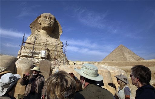Tourists listen to a historian in front of Sphinx in Giza, Egypt&#39;s most famous tourist attraction, Wednesday, Feb. 9, 2011.  The Pyramids, Egypt&#39;s most famous tourist attraction, reopened to tourists on Wednesday, as anti-government demonstrations entered their third week. Tens of thousands of foreigners have fled Egypt amid the chaos, raising concerns about the economic impact of the protests &#40;AP Photo&#47;Khalil Hamra&#41; <span class=meta>(AP Photo&#47; Khalil Hamra)</span>