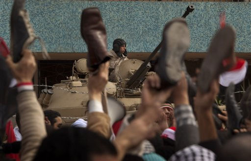 An army soldier sits on a armored vehicle as anti-government protesters hold their shoes in the air during a protest in front of  the state television building on the Corniche in downtown Cairo, Egypt Friday, Feb. 11, 2011. Mubarak refused to step down or leave the country and instead handed his powers to his vice president Thursday, remaining president and ensuring regime control over the reform process, which stunned protesters demanding his ouster, who waved their shoes in contempt and shouted, &#34;Leave, leave, leave.&#34; &#40;AP Photo&#47;Emilio Morenatti&#41; <span class=meta>(AP Photo&#47; Emilio Morenatti)</span>