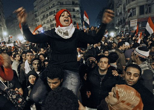 An Egyptian woman celebrates with other people after President Hosni Mubarak resigned and handed power to the military at Tahrir square, in Cairo, Egypt, Friday, Feb. 11, 2011. Egypt exploded with joy, tears, and relief after pro-democracy protesters brought down President Hosni Mubarak with a momentous march on his palaces and state TV. Mubarak, who until the end seemed unable to grasp the depth of resentment over his three decades of authoritarian rule, finally resigned Friday and handed power to the military. &#40;AP Photo&#47;Hussein Malla&#41; <span class=meta>(AP Photo&#47; Hussein Malla)</span>