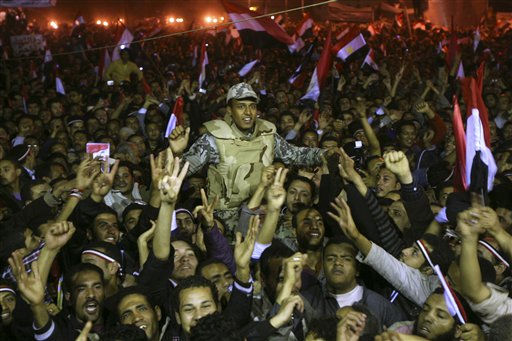 Egyptians celebrate as they carry an army soldier in Tahrir Square after President Hosni Mubarak resigned and handed power to the military in Cairo, Egypt, Friday, Feb. 11, 2011. Egypt exploded with joy, tears, and relief after pro-democracy protesters brought down President Hosni Mubarak with a momentous march on his palaces and state TV. Mubarak, who until the end seemed unable to grasp the depth of resentment over his three decades of authoritarian rule, finally resigned Friday and handed power to the military.&#40;AP Photo&#47;Ahmed Ali&#41; <span class=meta>(AP Photo&#47; Ahmed Ali)</span>