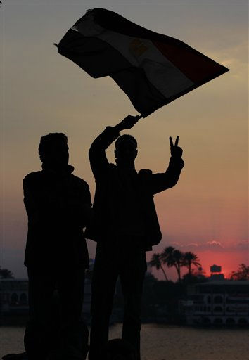 Anti-government protesters standing next to the Nile river wave an Egyptian flag and flash the victory sign at sunset, just before the news of the resignation of President Hosni Mubarak, who handed control of the country to the military, in downtown Cairo, Egypt Friday, Feb. 11, 2011. &#40;AP Photo&#47;Ben Curtis&#41; <span class=meta>(AP Photo&#47; Ben Curtis)</span>