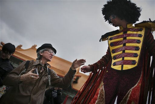 A Taiwanese man greets a member of the French La Compagnie des Quidams street theater group as they perform in disco attire at the Chiang Kai-shek memorial square in Taipei, Taiwan, Friday, Feb. 11, 2011. The performance was part of a month long cultural events of the Taiwan International Festival of Arts. (AP Photo/Wally Santana)
